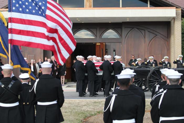 Casket teams position the caskets on the caissons, while the escort team salutes.