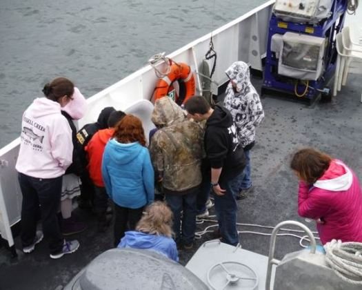 The group examines bottom samples collected by the Rainier.