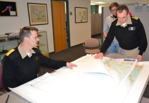 Rear Admiral Gerd Glang and Capt. Shep Smith inspect sample charts submitted by new print agents.