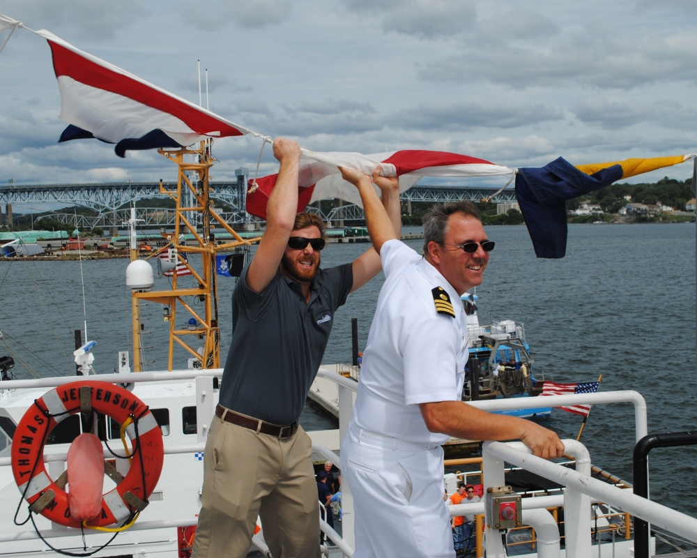 LCDR Jim Crocker and Alex Ligon wrestle with wayward semaphore flags
