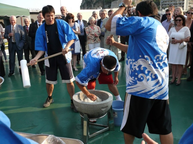 Crew members of the training ship Kojima of Japan Coast Guard demonstrate a traditional method of making rice cakes during the event on board the Kojima