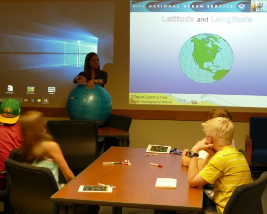 Jessica Ramsay teaches campers about latitude and longitude using a yoga ball globe.
