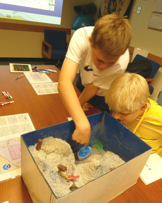 """Campers examine the inside of a sounding box after graphing depths measured through its mesh """"water"""" surface."""