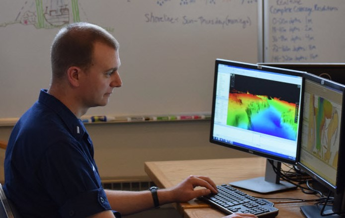 Lt.j.g. Bart Buesseler review multibeam bathymetry data in the shore team base of operations room.