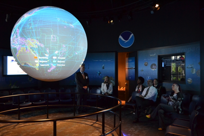 Dr. Shachak Pe'eri, Sladjana Maksimovic, and Megan Bartlett of Coast Survey's Marine Chart Division, demonstrate Coast Survey data on Science on a Sphere.