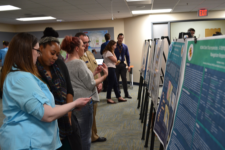 NOAA's Christie Ence (left), Megan Bartlett (third from left), and Noel Dyer (right) explain their posters to attendees of the poster symposium at the University of Maryland.