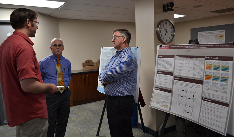 NOAA's Colby Harmon (center) and Craig Winn (right) talk nautical charting with capstone course instructor Dr. Jonathan Resop at the poster symposium.