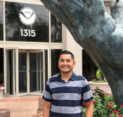 Brian Martinez stands in front of the NOAA Headquarters building