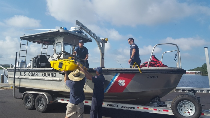 Alex Ligon (NOAA NRT1) works with USCG Boatswain Mate (BM) 1 Lee Durfee, BM2 Collin Blugis, and Machinery Technician 3 Matt Kemp to load the ASV on the USCG vessel.