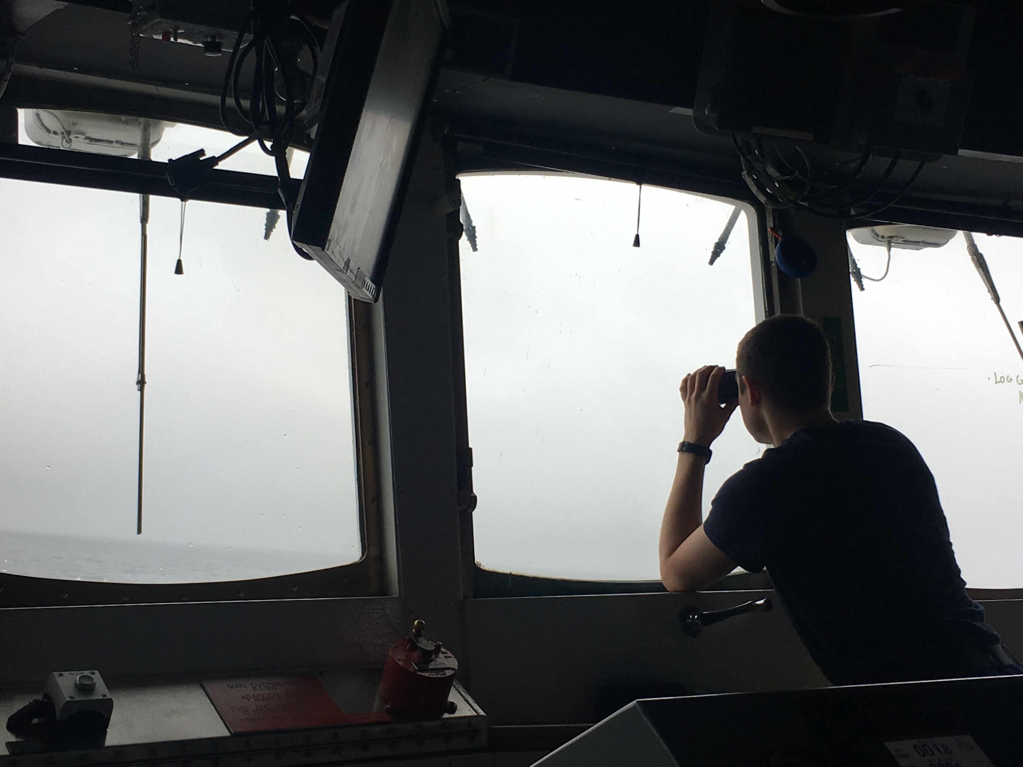 A NOAA Corp officer watches for hazards to navigation on board NOAA Ship Fairweather.