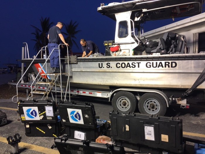 Mike Annis (right), NOAA scientist and lead of NOAA's Mobile Integrated Survey Team (MIST), and LCDR Jonathan French, mount side scan sonar on a Coast Guard vessel in Key West.
