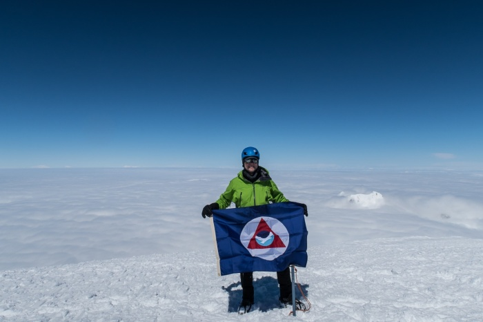 Cmdr. Van Waes holds the NOAA flag atop the summit of Mount Fairweather
